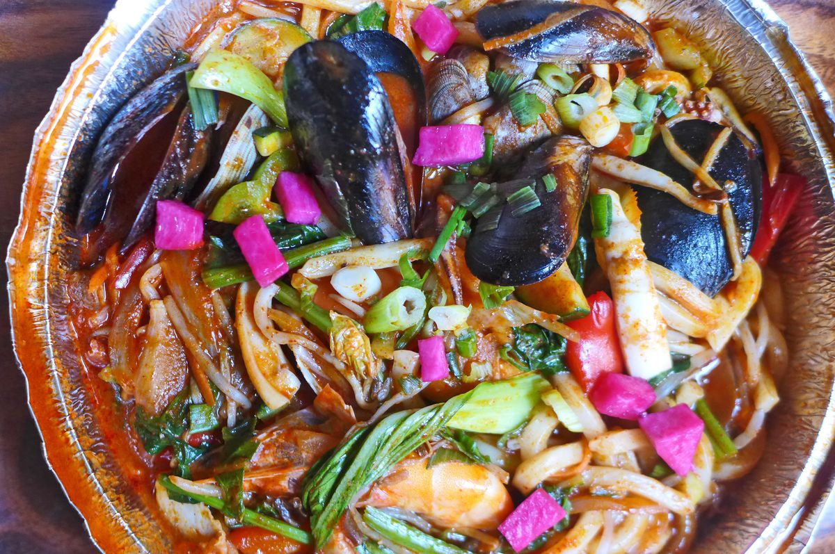 A takeaway container with a colorful seafood dish composed of mussels, noodles, pink radishes, and green bok choy