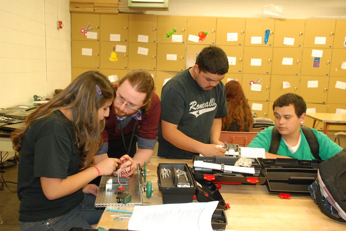 Roncalli Middle School social studies teacher Michael Lonsberry, center left, works with students on a robotics project in April. Roncalli is the lowest performing middle school in the state. As part of the district's turnaround effort, it is rolling out a science, technology, engineering, and math program.