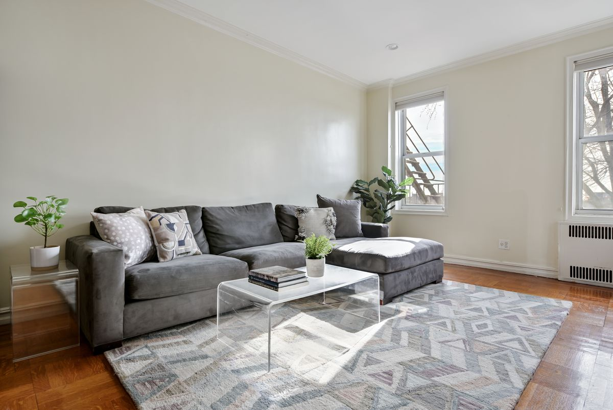 A living area with hardwood floors, two windows, base moldings, a grey rug, and a dark grey couch.