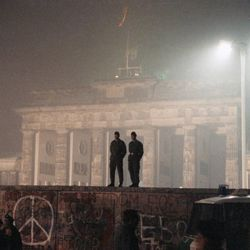 This was the scene when two East German border guards patrolled atop of Berlin Wall with the illuminated Brandenburg Gate in background, in Berlin, Nov. 14, 1989.