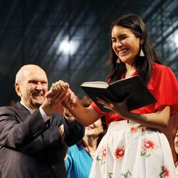 President Russell M. Nelson of The Church of Jesus Christ of Latter-day Saints helps Isabela Castellano as she directs a song at the end of a Latin America Ministry Tour devotional in Quito, Ecuador on Monday, Aug. 26, 2019.