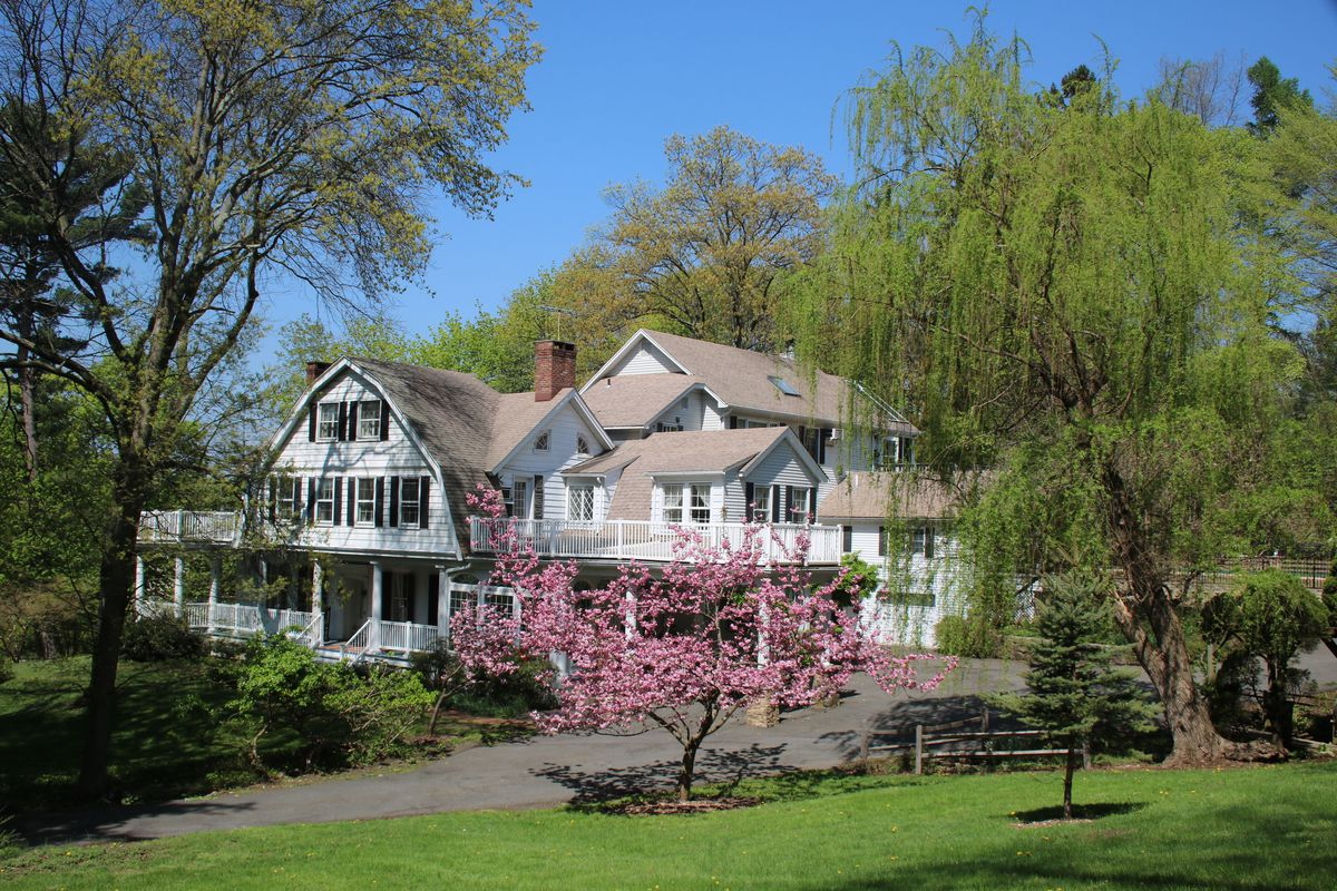 Exterior shot of a large, white Dutch Colonial home with multiple porches and roof gables set among trees.