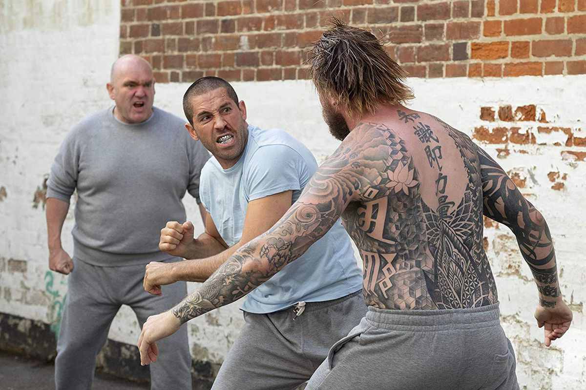 Scott Adkins throws a punch in a prison yard in Avengement