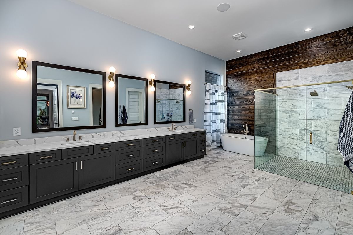 Large bathroom with expansive double vanity, soaking tub and glassed-in shower.