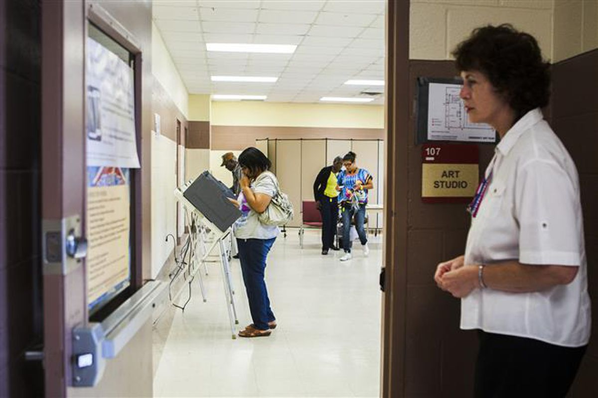 Linda-Marie Goetze (right), officer, Shelby County Election Commission, waits patiently outside a doorway of an early voting precinct, Dave Wells Community Center, for voters as Mary Wilkins (second from left) ponders a decision at a voting booth in North Memphis.