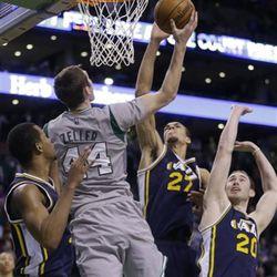 Boston Celtics center Tyler Zeller (44) goes up for the game-winning shot against Utah Jazz guard Rodney Hood (5), center Rudy Gobert (27) and forward Gordon Hayward (20) during the second half of an NBA basketball game in Boston, Wednesday, March 4, 2015. The Celtics won 85-84. (AP Photo/Elise Amendola)