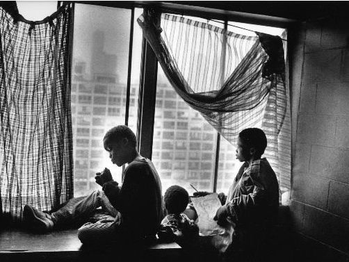 Harvey Reynolds (left) and Michael Reynolds sit in the window of their ninth-floor Cabrini-Green apartment in 1992. They were best friends of Dantrell Davis, a 7-year-old boy killed by a sniper as he walked to school. (Photo by John H. White.)