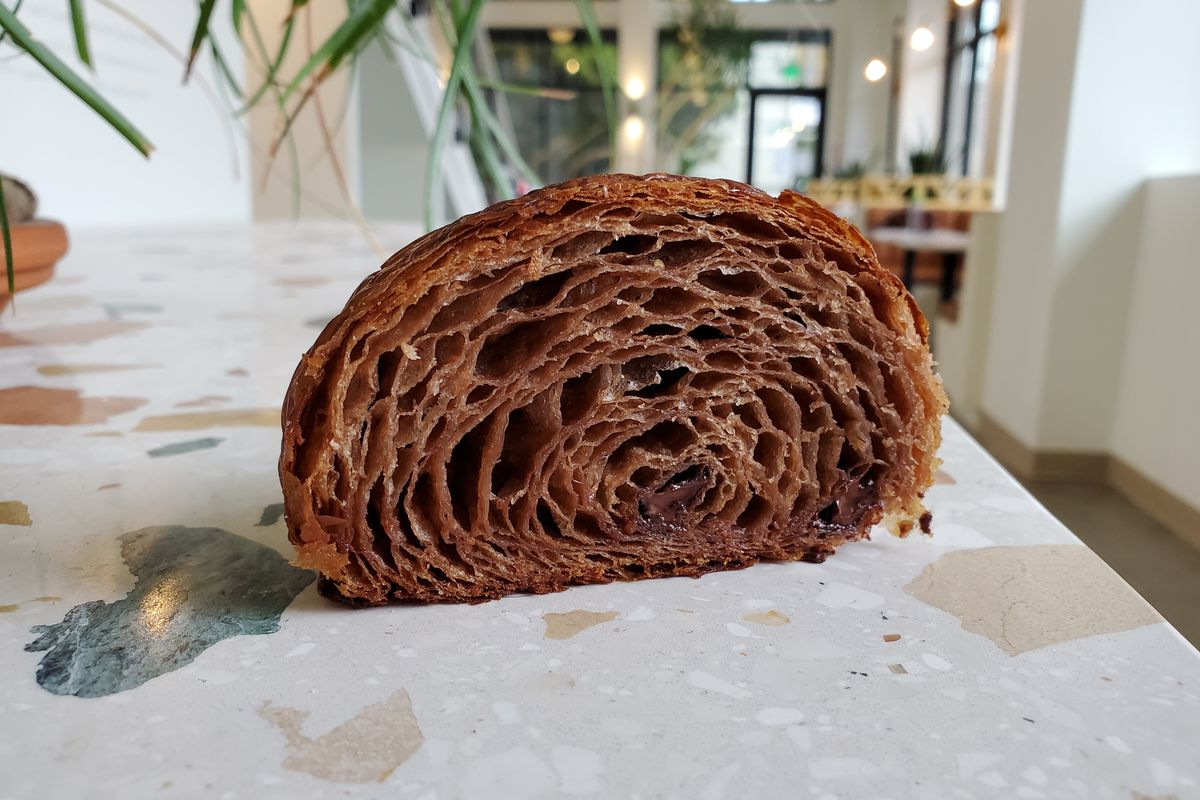 A closeup of a buckwheat croissant, shown as a cross-section on a marble countertop