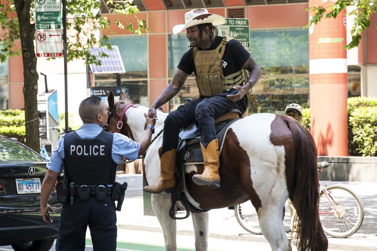"""Adam Hollingsworth, 33, otherwise known as """"The Dread Head Cowboy,"""" greets a Chicago Police officer as he rides his horse Prince in the Loop"""