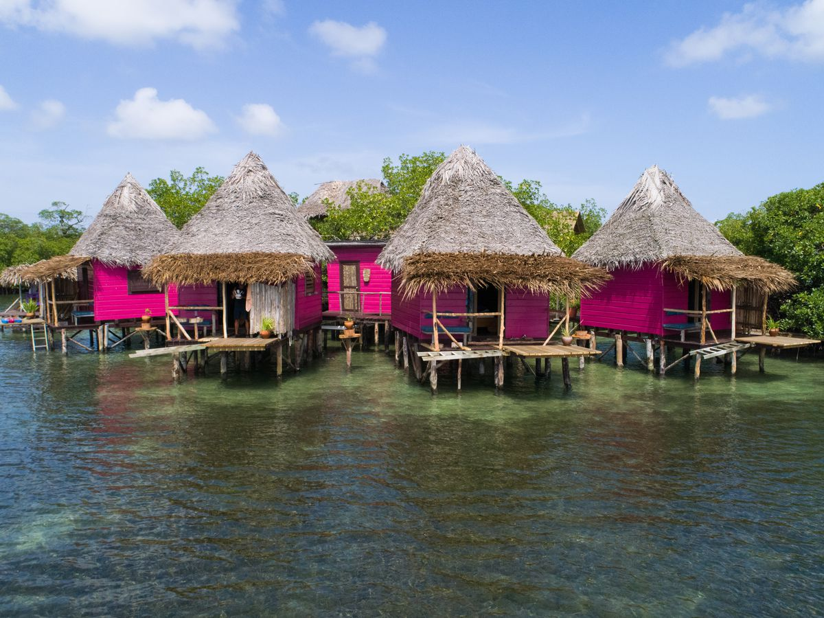 Bright pink huts with thatch-style roofs sit over the water in Panama.