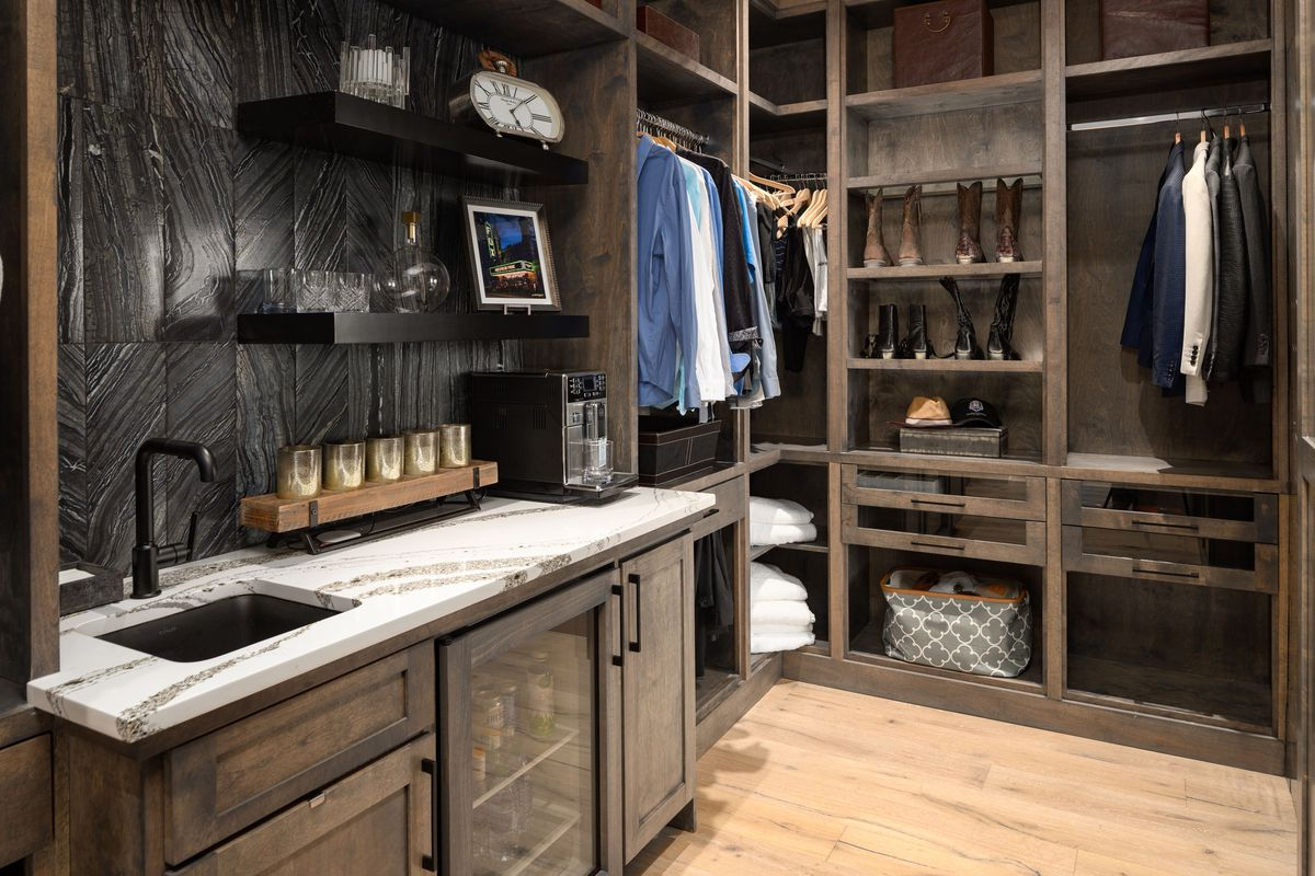 A master closet with a wine bar and watch safe and jackets hanging.