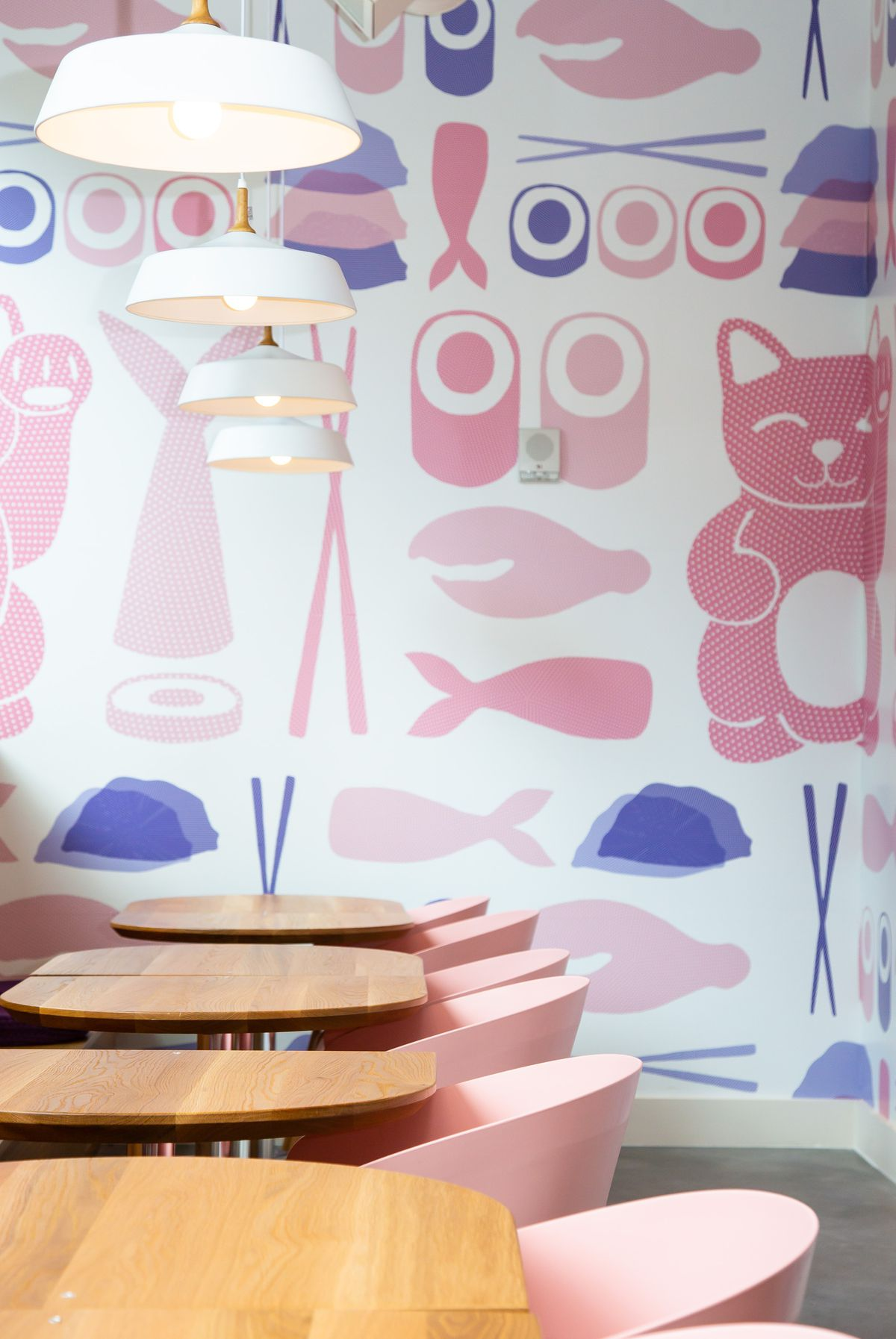 A row of tables with pink chair and a wall filled with pastel pink and purple paintings of lucky cats, chopsticks, sushi rolls, and fish