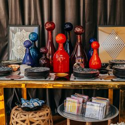 <b>Elizabeth Lyons</b> handblown colored glass jars with over-sized stoppers, $375-$695. Underneath: a vintage 1970s <b>Milo Baughman</b> brass and smoked glass dining table, $,1650