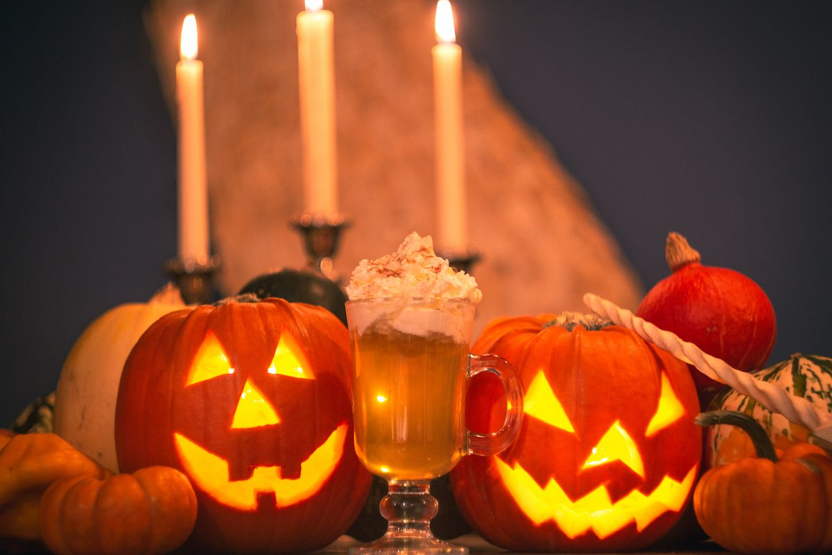 Two carved pumpkins sitting side by side with a cup in the middle and candles in the background