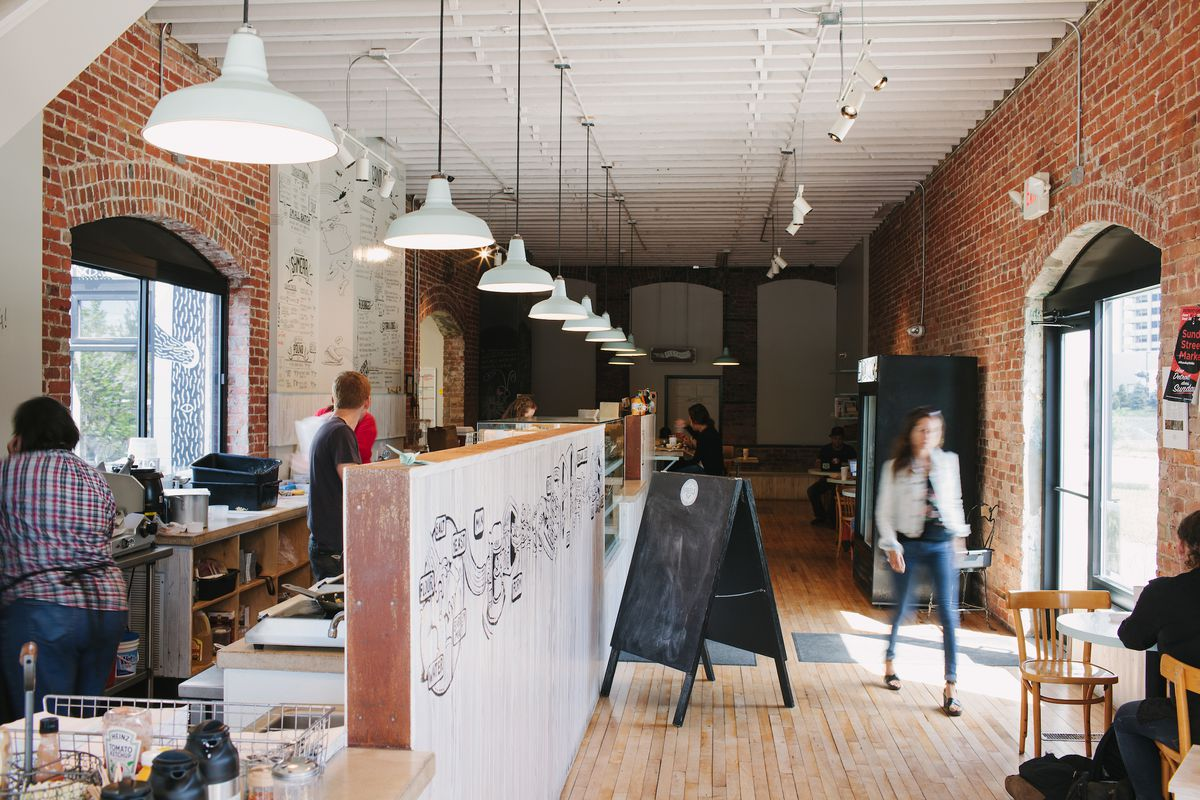 A wall separates the bagel assembly line from the line to place orders at DIB in Corktown. The restaurant features white and red brick walls with white industrial pendant lights.