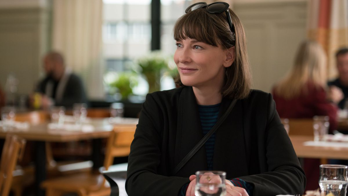The actress Cate Blanchett plays the role of Bernadette in Where'd You Go, Bernadette. She sits in a restaurant at a table. She has on a dark colored coat and a pair of round sunglasses sits perched on top of her head.