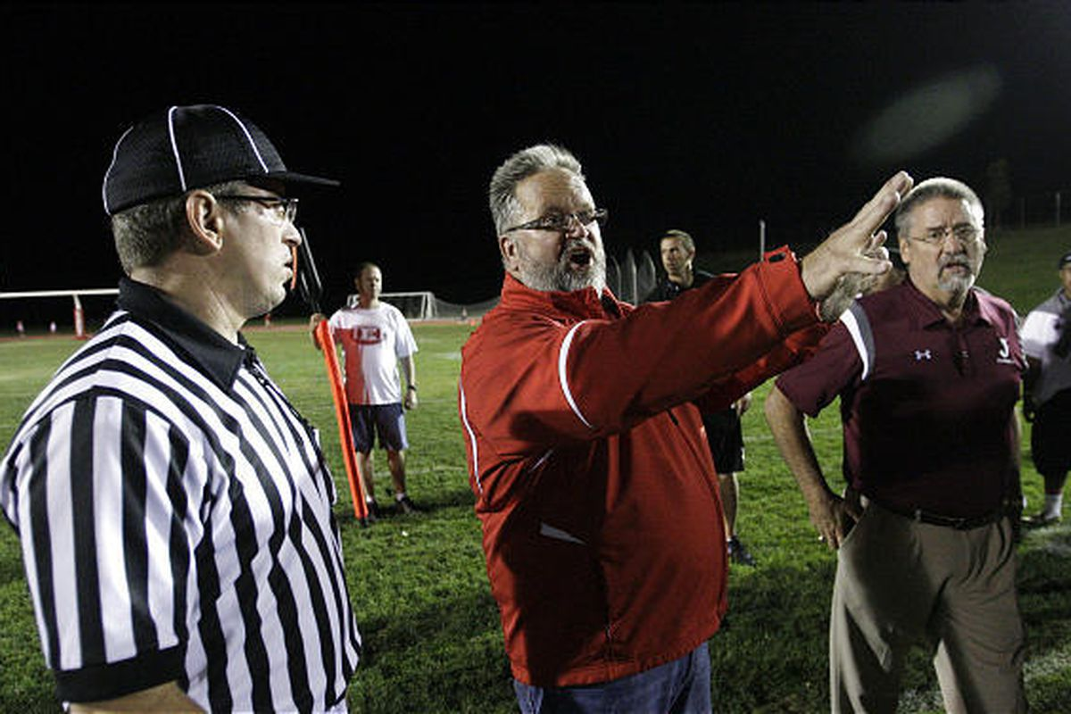 East High principal Paul Sagers confers with referees and coaches as Salt Lake City Fire evacuate fans and players from the  East High School stadium after a fire broke out in a facility building at the field in Salt Lake City, Friday, Aug. 31, 2012.