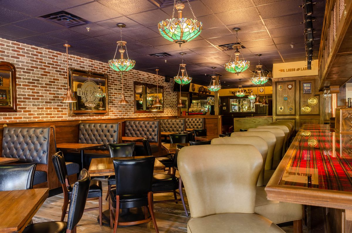 A shot of the red plaid bar with beige leather bar stools overlooking the dining room with black leather booths and tables