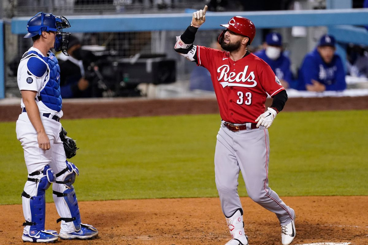 Cincinnati Reds right fielder Jesse Winker (33) gestures as he crosses home plate after hitting a two-run home run during the tenth inning as Los Angeles Dodgers catcher Will Smith (L) looks on at Dodger Stadium.