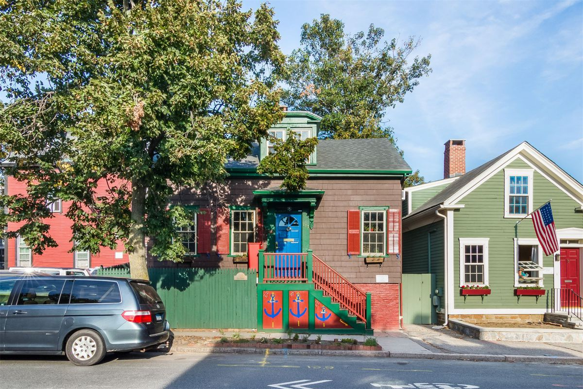 Small timber-framed cottage with green and red trim and three anchors painted on the front stairs.