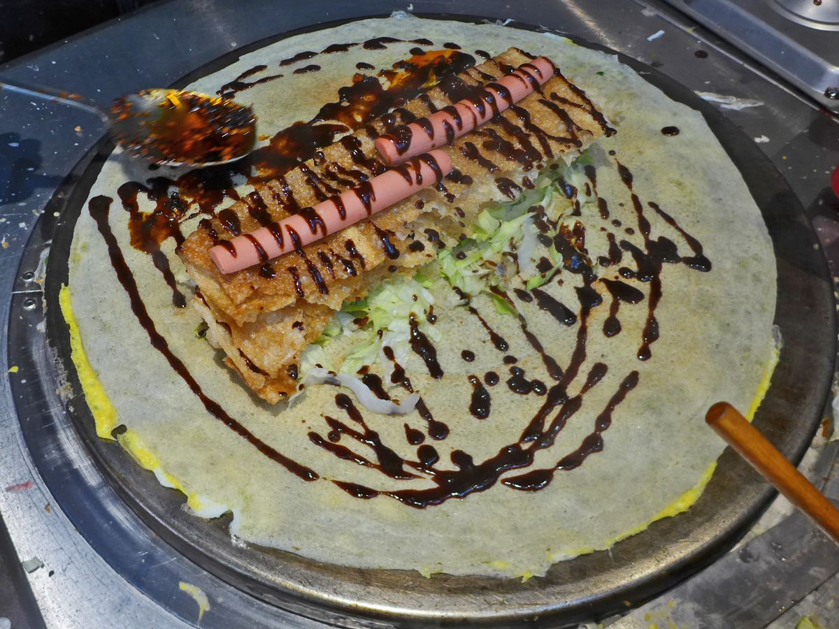 A round pancake on a grill with all sorts of toppings.