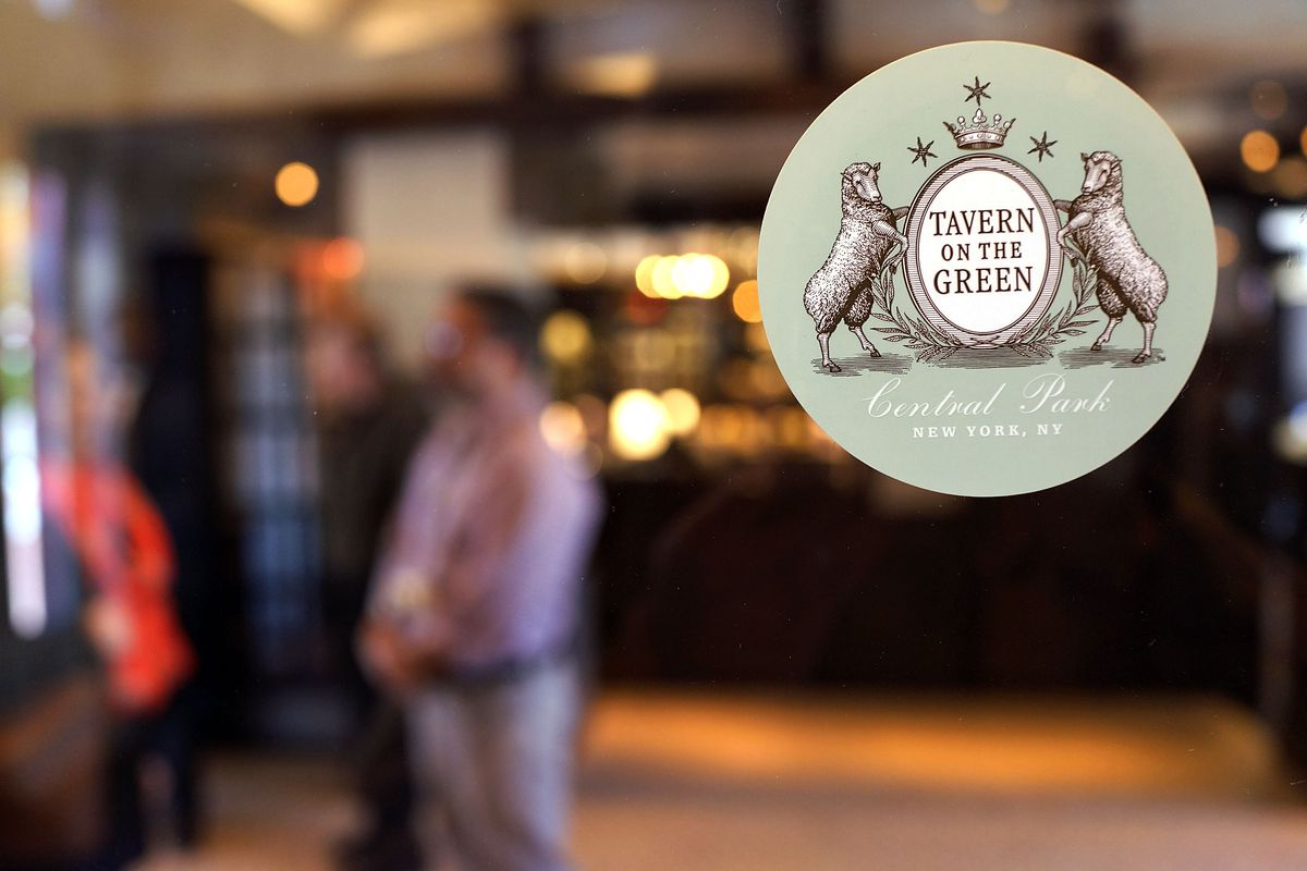 Pale green Tavern on the Green logo in the upper righthand side of a window with customers in the background