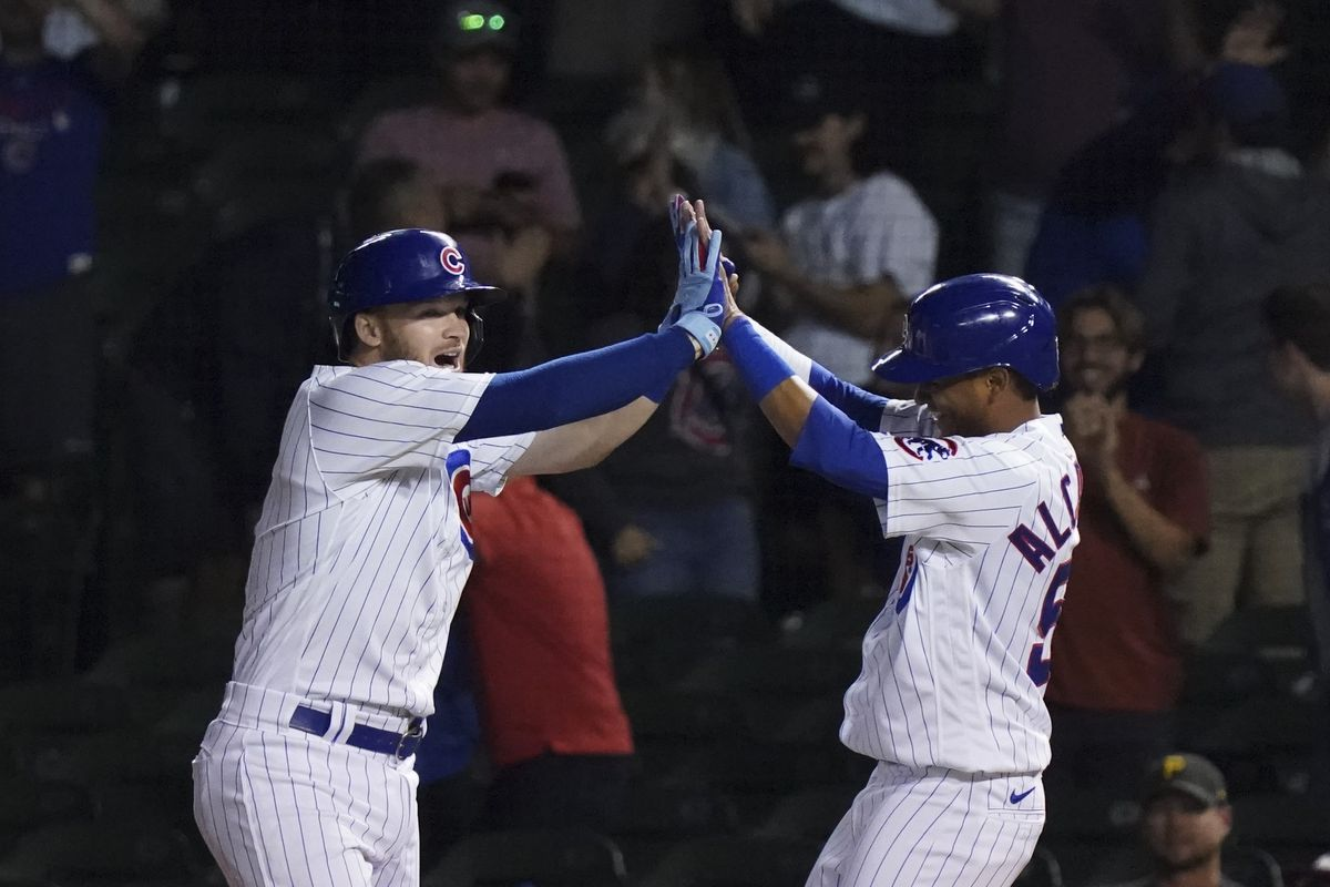 Ian Happ and Sergio Alcantara celebrate the Cubs' 6-5, 11-inning victory over the Pirates on Thursday night at Wrigley Field.