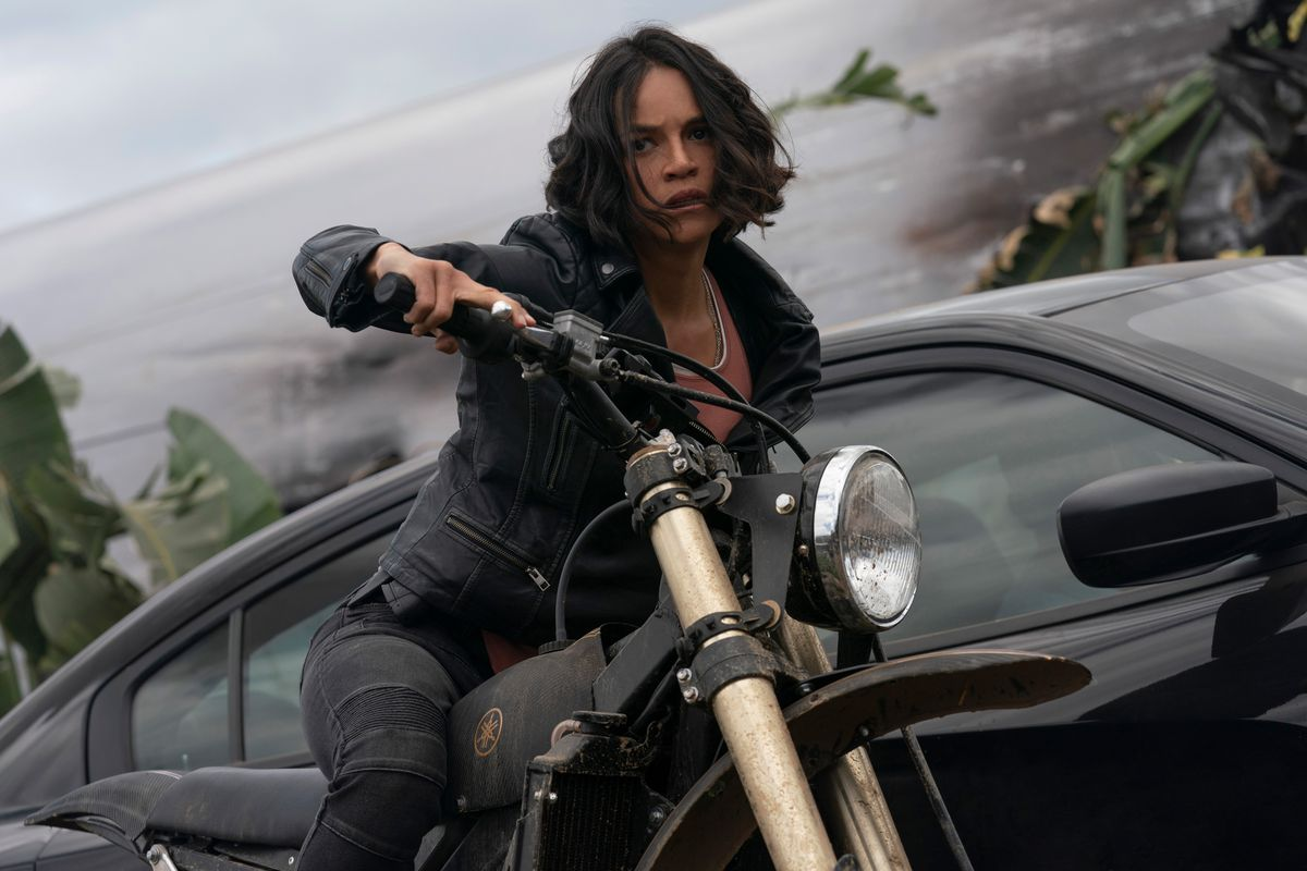 Letty (Michelle Rodriguez) on a motorcycle in front of a car in F9