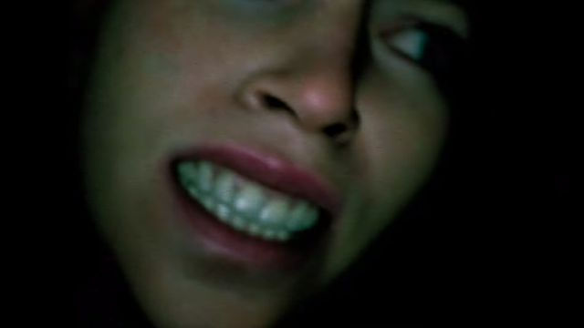 A close up of a woman's anguished face in a dark setting