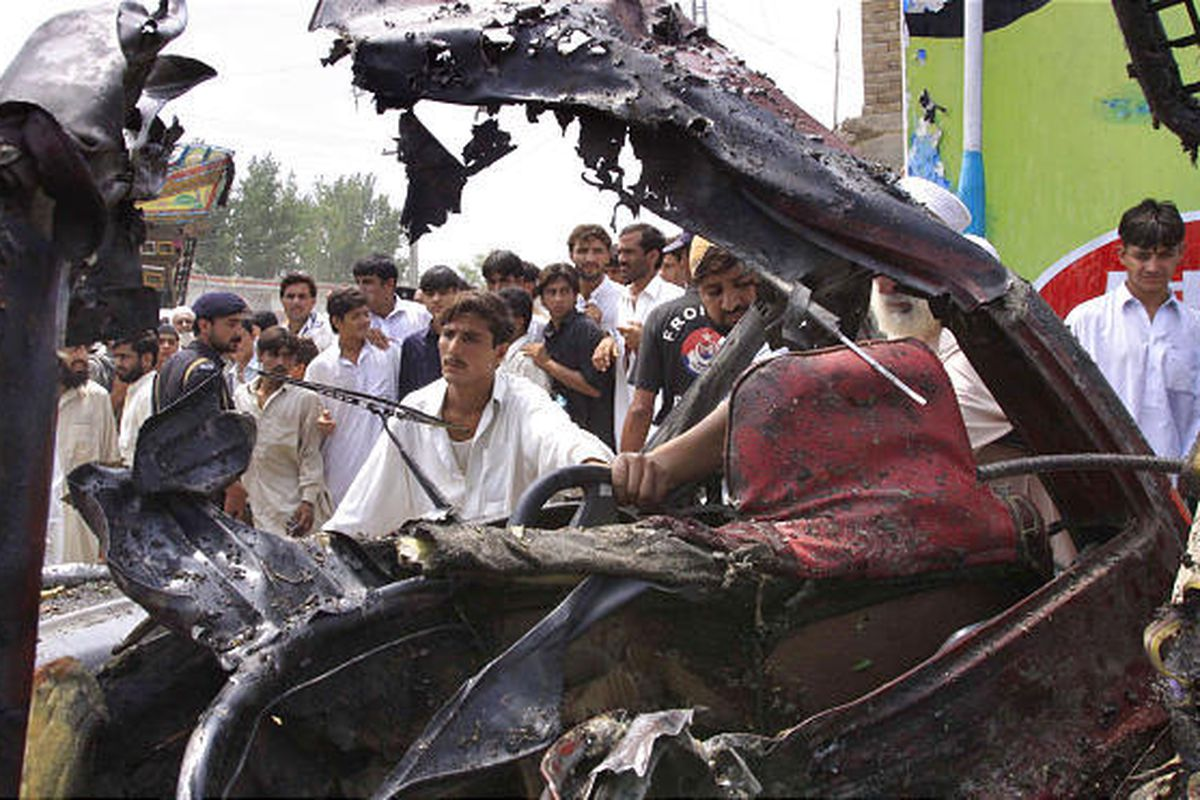 Local residents look to the wreckage of a damaged truck after a bomb blast in the Shabqadar area of Charsada district near Peshawar, Pakistan, on Monday.