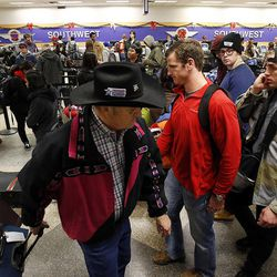 Travelers line up at Salt Lake City International Airport as flights were delayed during a snowstorm, Thursday, Dec. 19, 2013.