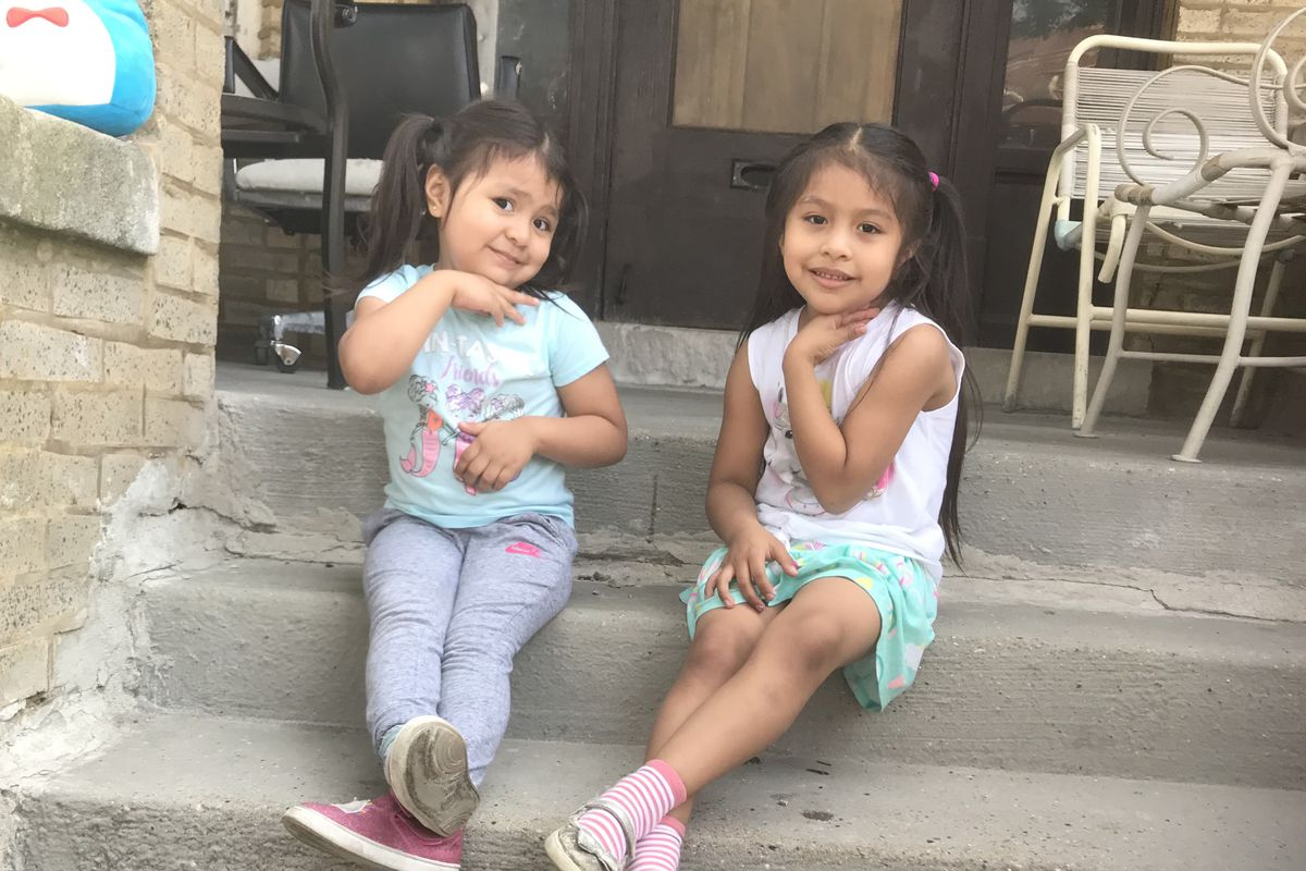 Two young girls sit on the front porch of their Chicago home. Their mother worries about who will care for them if their preschool closes.