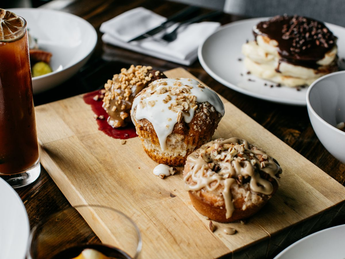 Muffins, bloody marys, and more on a wooden cutting board.