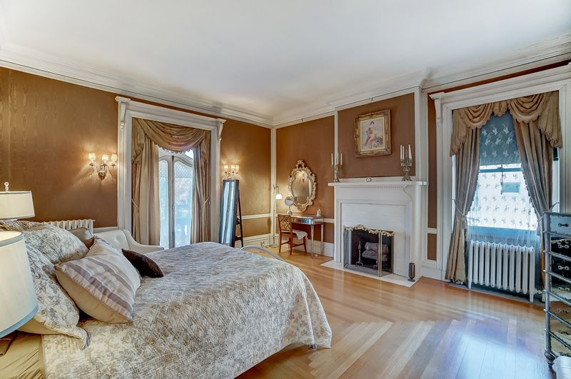 A bedroom has gold walls, white trim, a fireplace, and a large bed that looks onto the fireplace.