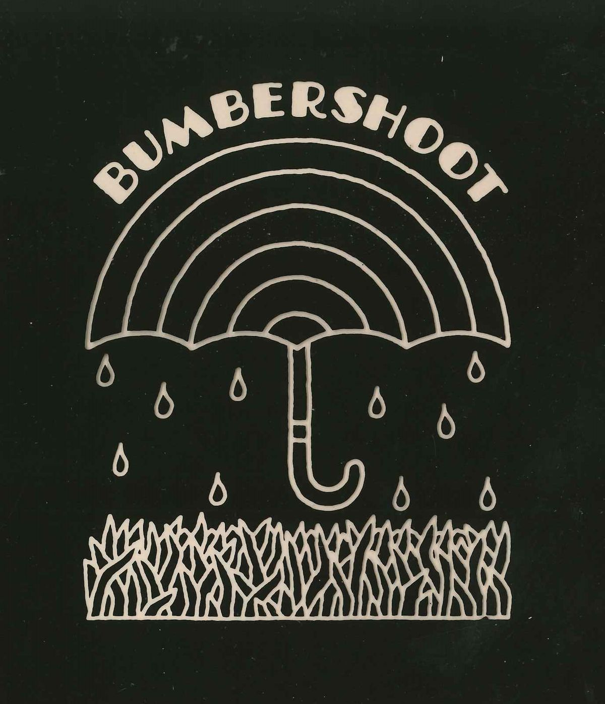 A black-and-white logo. On a black background, an umbrella with a rainbow-like striped design and raindrops coming down on it. There's grass below, and the text BUMBERSHOOT lines the top of the umbrella.