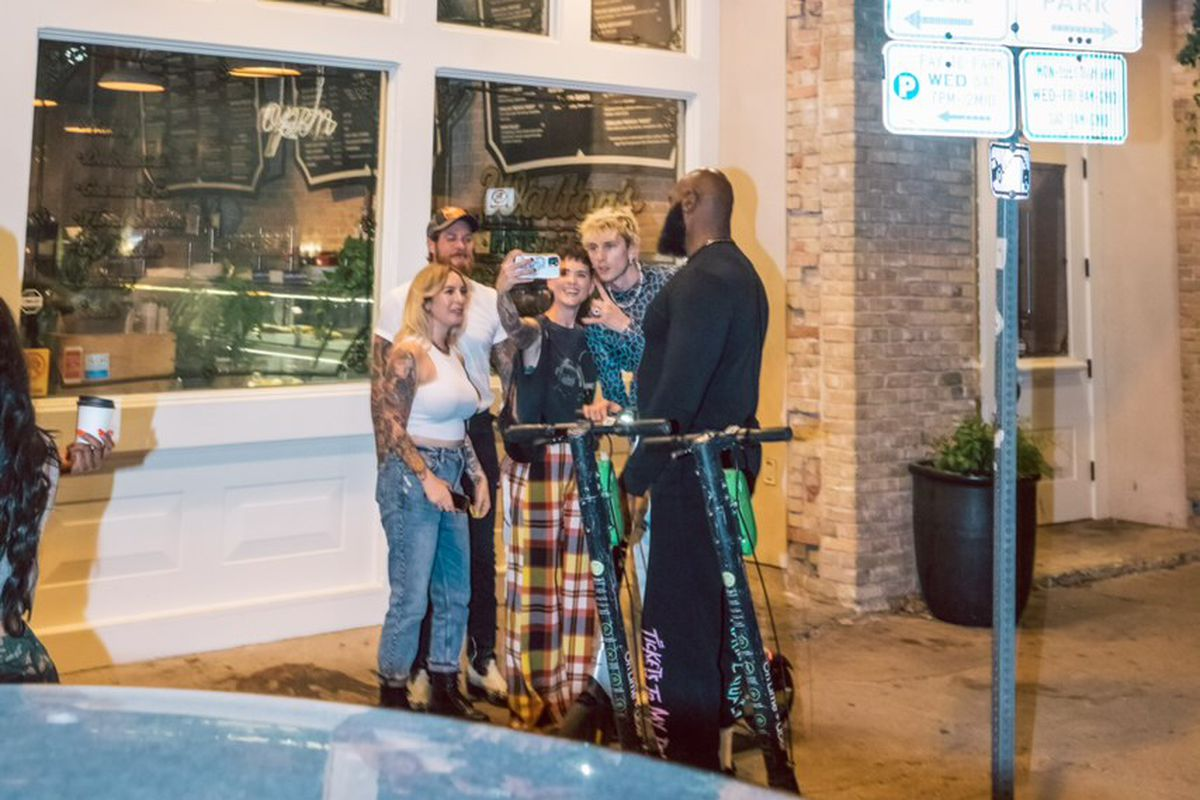 A group of people posting for a selfie photo in front of a restaurant.