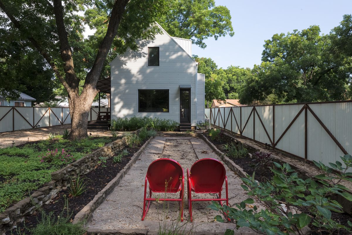 backyard of modern farmhouse style small two story house with contemporary fence and two red chairs