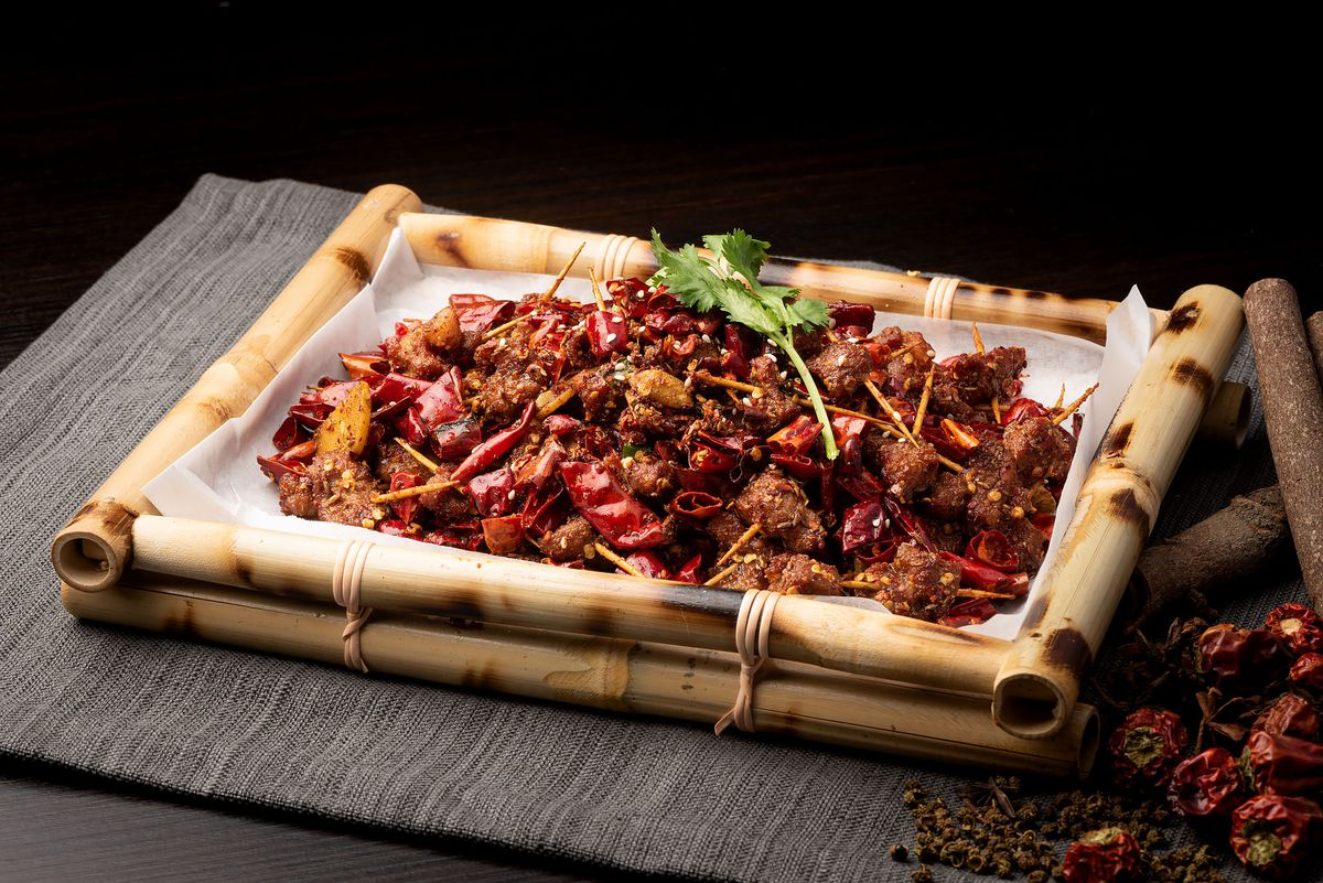 A bamboo plate of toothpick lamb with lots of peppers.