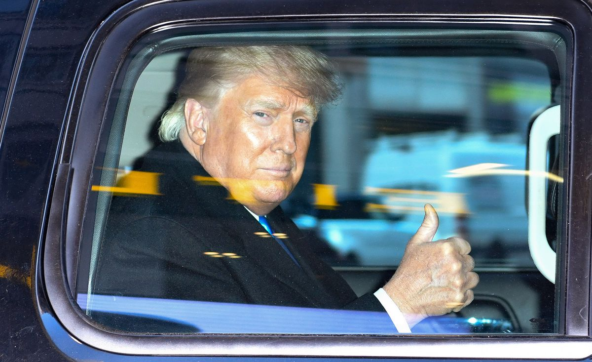 Donald Trump gives a thumbs-up sign through the window of his car.