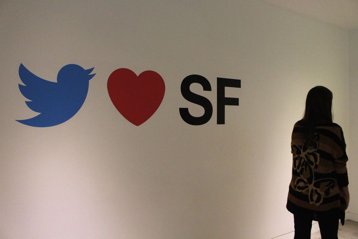 A sign on a wall reading that Twitter loves San Francisco, featuring the Twitter bird and a red heart.