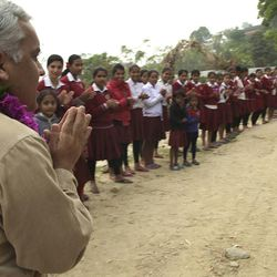 After leaving his village to receive a degree in engineering, Bishnu Adhikari returned to his home in Nepal with a determination to help improve the living conditions of the area. School children line the street to greet Adhikari, who has built many schools in the country.