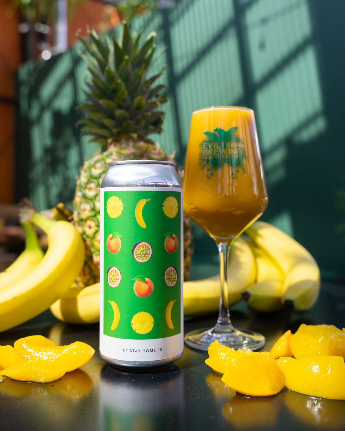 A colorful green and yellow beer stands on a table against a backdrop of bananas and pineapple