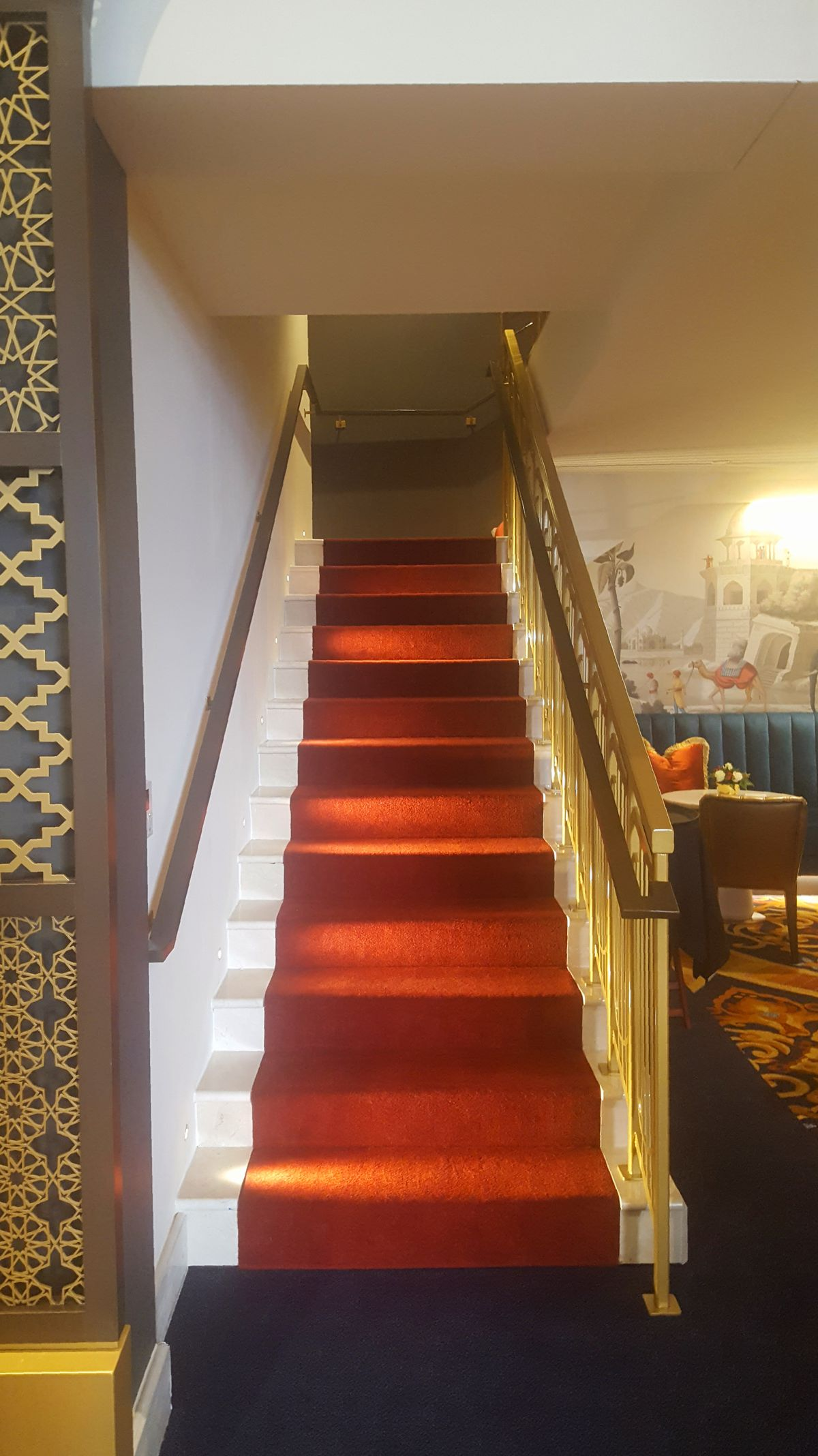A photo of a velvet staircase that leads to another lounge on the second floor.