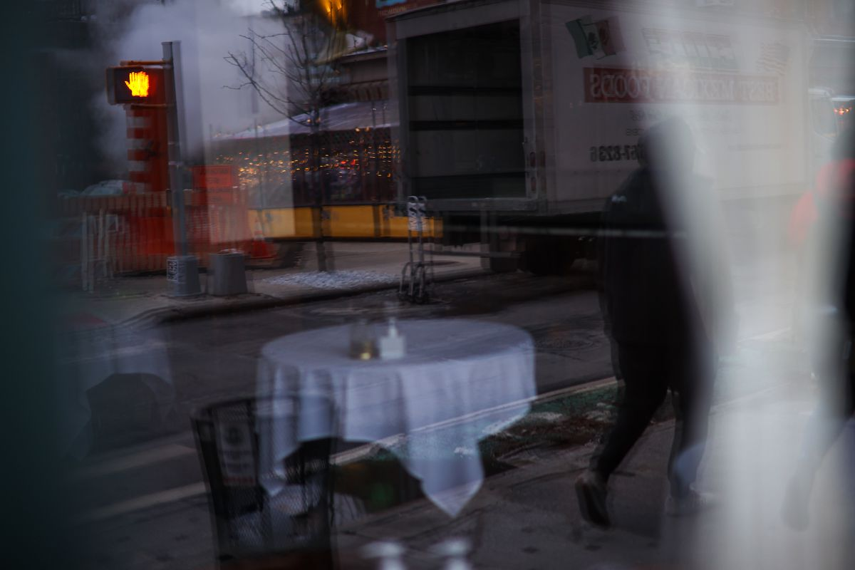 A restaurant dining room with a table covered in a white tablecloth viewed through a window