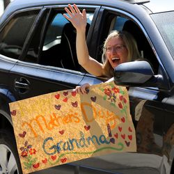Emily Brand waves at her grandmother Sharon Hansen, as residents at The Ridge Cottonwood assisted living center in Holladay watch family members parade with signs, balloons and waves for Mother's Day on Saturday, May 9, 2020.