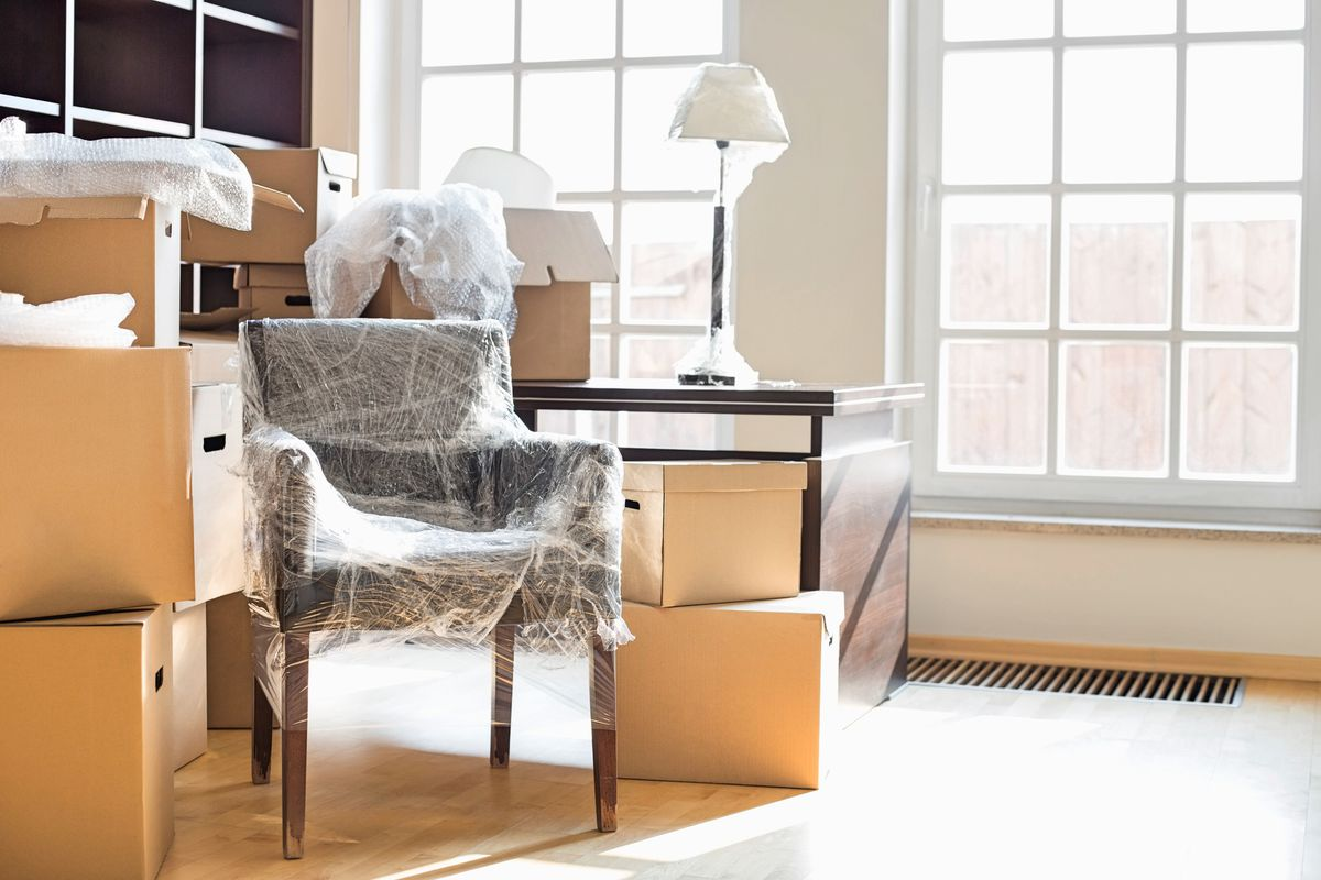 Moving boxes and furniture wrapped up in the office of a home.