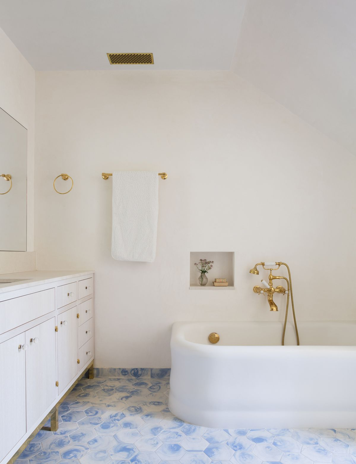 A bathroom. There is a white bathtub with brass fixtures. The floor is decorated in blue and white tiles. There is a white vanity which has a mirror hanging over it. The walls are painted white.