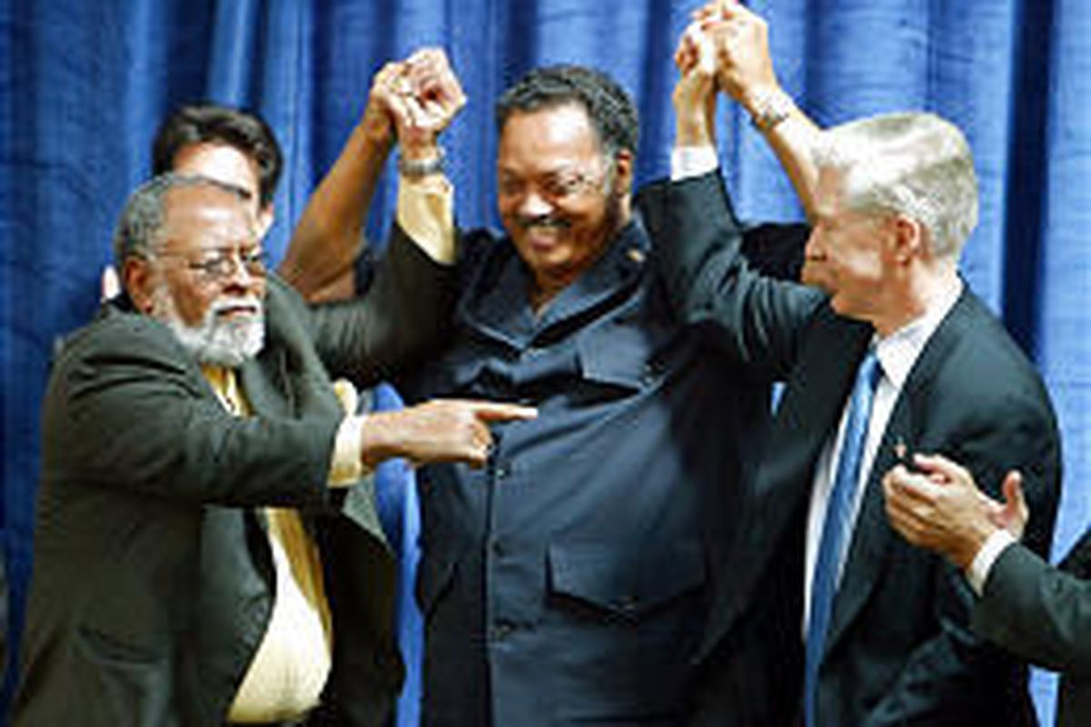 Rev. Jesse Jackson, center, holds up the hands of the Rev. Cecil Williams, left, and California Gov. Gray Davis, right, during a rally for the governor in San Francisco.