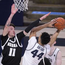 Utah State guard Marco Anthony (44) takes a shot as Nevada guard Kane Milling (11) defends during the first half of an NCAA college basketball game Sunday, Feb. 28, 2021, in Logan, Utah.