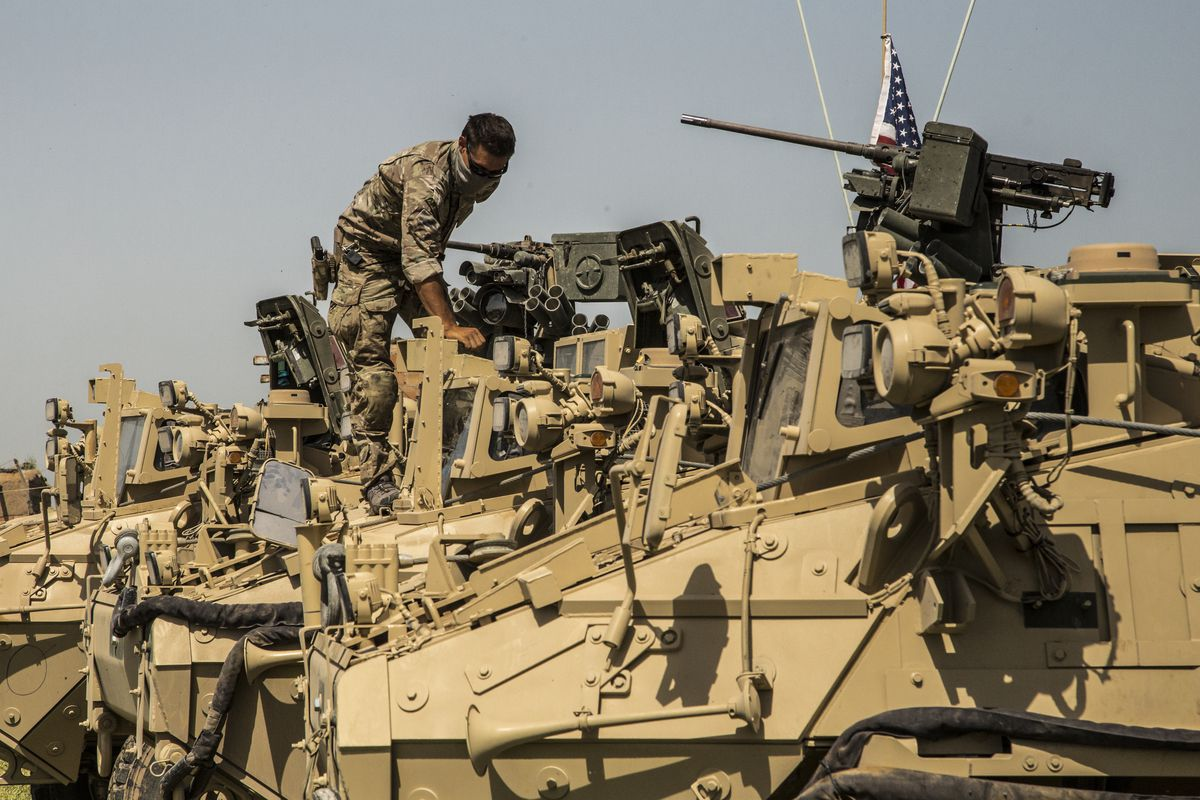 A soldier inspects an armored vehicle flying the US flag; other armored vehicles are in a line behind the one he is standing on.